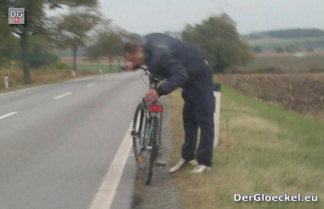 Als der Mann merkte, daß er fotografiert wurde, tat er so als ob er Probleme mit seinem Fahrrad hatte und verließ die Straße über das offene Feld